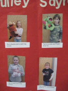 Students hold a stuffed animal and count their feet plus the animal's feet to illustrate the concept